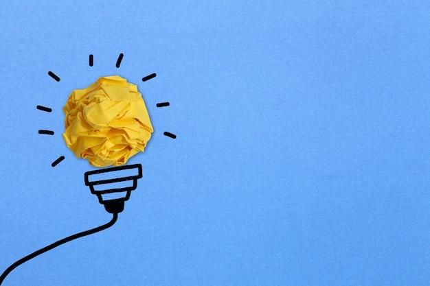 Spherical wrinkled paper and hand drawn black line light bulb idea