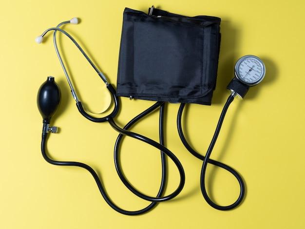 노란색 배경에 혈압계 클로즈업입니다. 혈압을 측정하는 의료 기기
