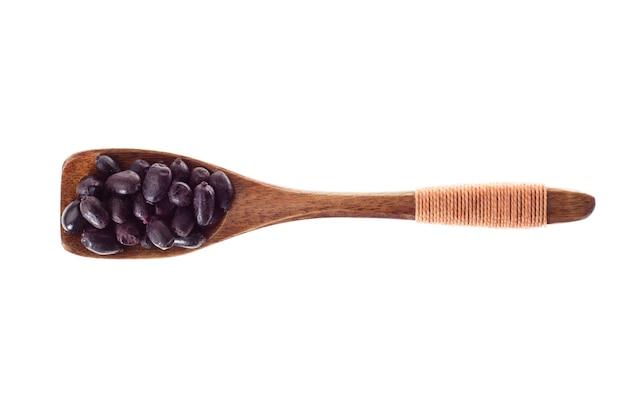 白い背景に、上面に分離された木のスプーンで乾燥した黒のスパイス メギ