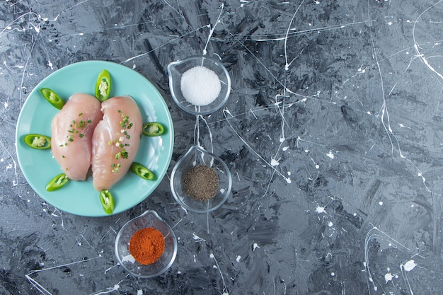 Чаши для специй и куриная грудка на тарелке, на мраморном фоне.