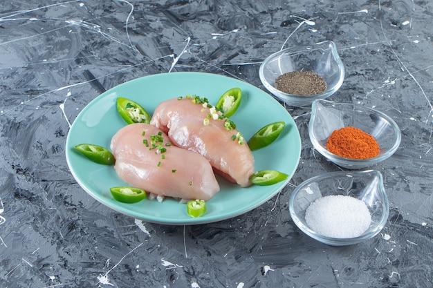 Чаши для специй и куриная грудка на тарелке, на мраморной поверхности.