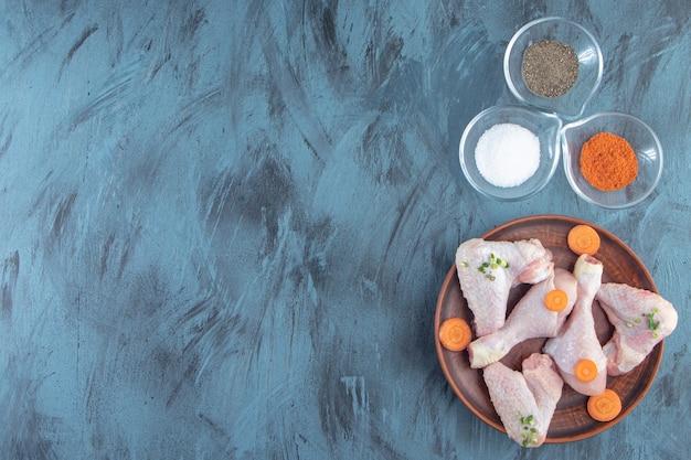 Миски для специй и куриное мясо на деревянной тарелке, на синем фоне.