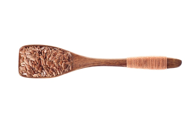 Spice flax seeds in wooden spoon isolated on a white background