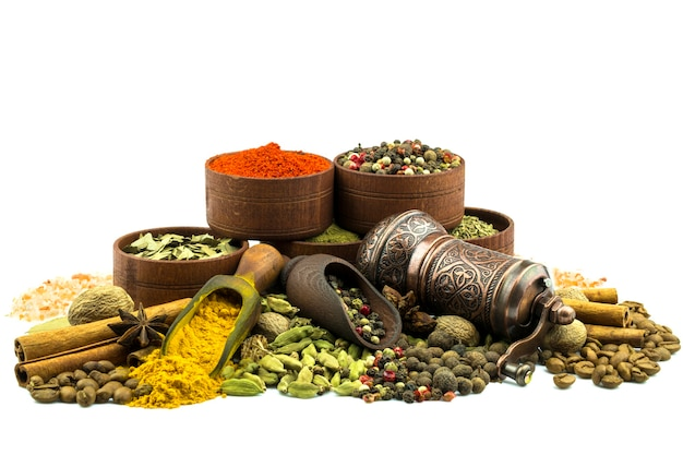 Spice mill, sprinkled spices and spices in a wooden bowl isolated on a white background.