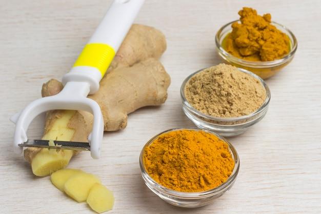 テーブルの上に生姜の根と野菜カッター、生姜とターメリックパウダーをセットしたスパイス