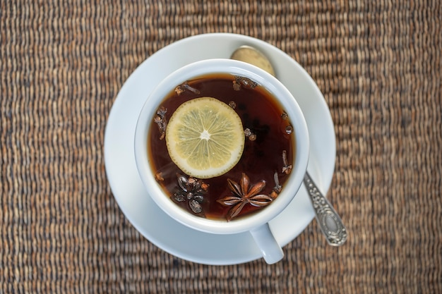 Чай со специями, состоящий из корицы, черного перца, кардамона, звездчатого аниса, лимона, гвоздики и горячего яблочного сока. крупным планом, вид сверху. чай с корицей. чайный напиток