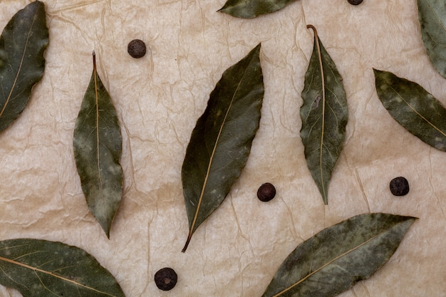 月桂樹の葉と黒コショウのボールとスパイスのテクスチャです。美しい素朴なバニラの背景。上面図