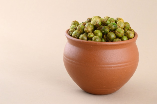 Spiced fried green peas {chatpata matar} indian snack. dried salted green peas in clay pot.