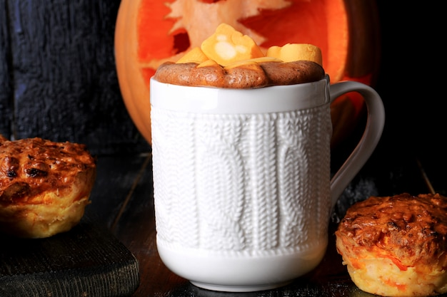 Spiced pumpkin coffee with marshmallows and pumpkin muffins on a black wooden background