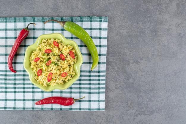 Пряный рис с нарезанным перцем в зеленой миске. фото высокого качества