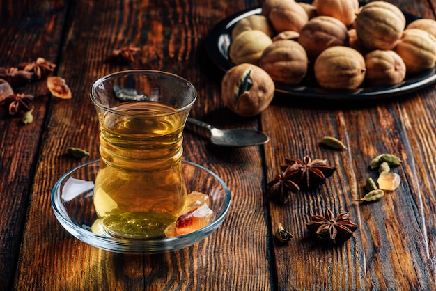 Пряный чай со звездчатым анисом, кардамоном и сушеным лаймом в стакане армуду на деревянной поверхности