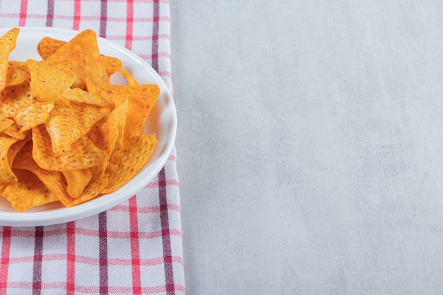 Spiced triangle chips on white plate on stone.