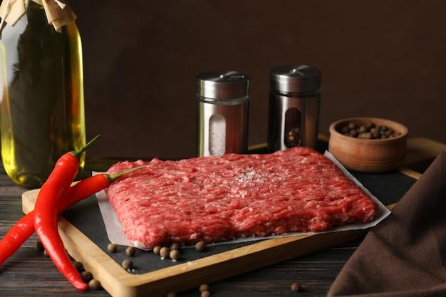 Специи и разделочная доска с мясным фаршем на деревянном, крупным планом