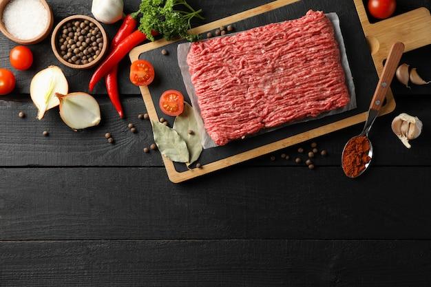 Специи и разделочная доска с мясным фаршем на деревянном, вид сверху