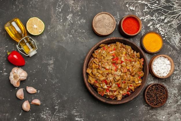 スパイスと皿にんにく赤ピーマンの油のボトルは、インゲンのプレートとスパイスの4つのボウルの横にあります