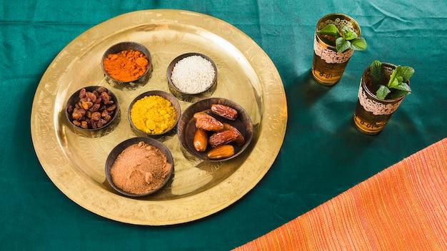 Специи и сухие фрукты на подносе возле чашки с напитком