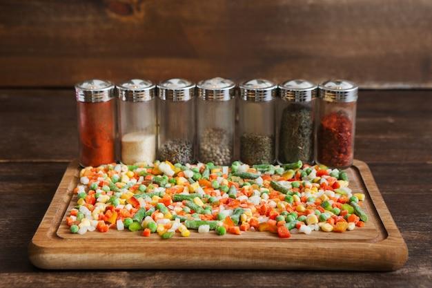 Специи и замороженные овощи на разделочной доске