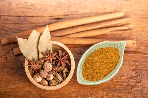 木製の背景にカレーカレー粉クローブカルダモンシナモンキャラウェイを調理するためのスパイスとハーブの成分