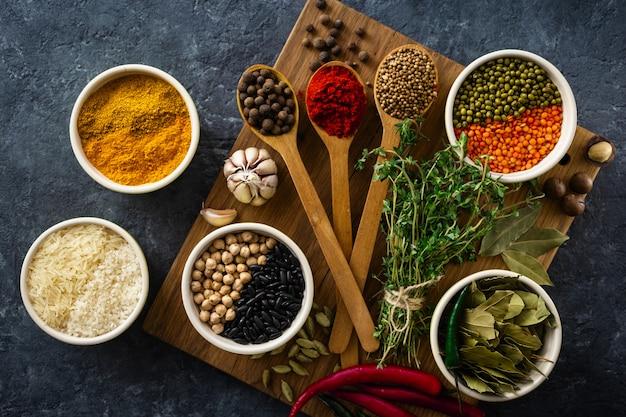 暗いトップビューでスパイスとハーブ、米、さまざまな豆