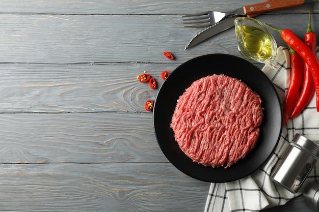 Специи и тарелка с мясным фаршем на деревянном, вид сверху