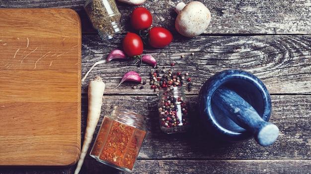 Специи и овощи на кухонном столе, вид сверху. деревенский стиль.