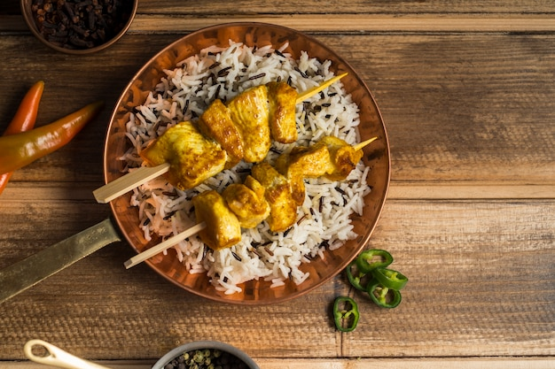 Spices around frying pan with chicken kebab