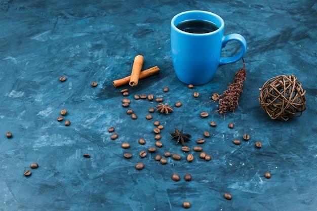 Spezie e tazza di caffè su uno sfondo blu scuro