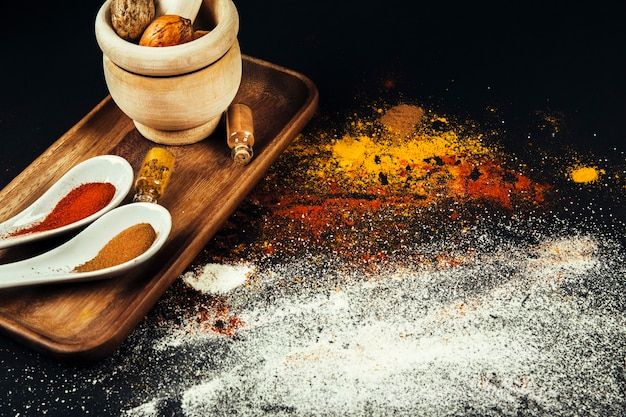 Spices composition with mill and spoons on board