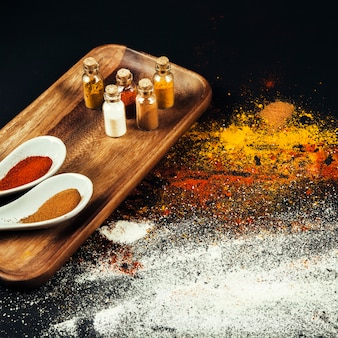 Spices composition with spoons and bottles on wooden board