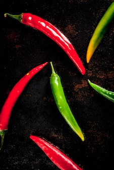 Spices for cooking spicy red and green chilli peppers on old metal rusty background