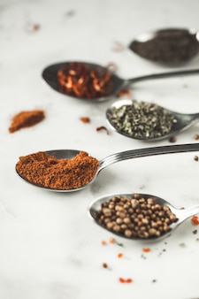 Spices in different spoons on stone marble table .