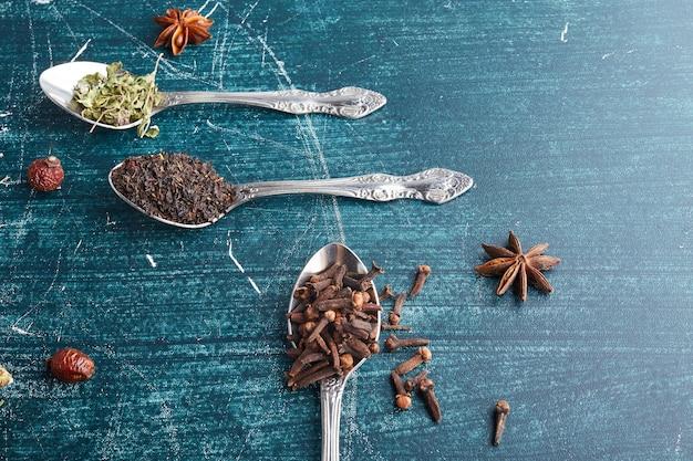 Spezie e foglie di tè secche in cucchiai metallici.