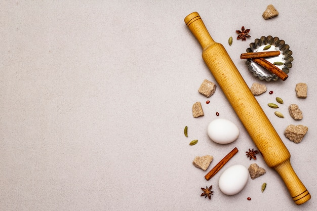 Spices, eggs, brown lump sugar, cupcake baking dish and a rolling pin. light