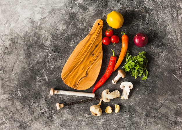 Spices and fresh vegetables with wooden chopping board against stained grunge background
