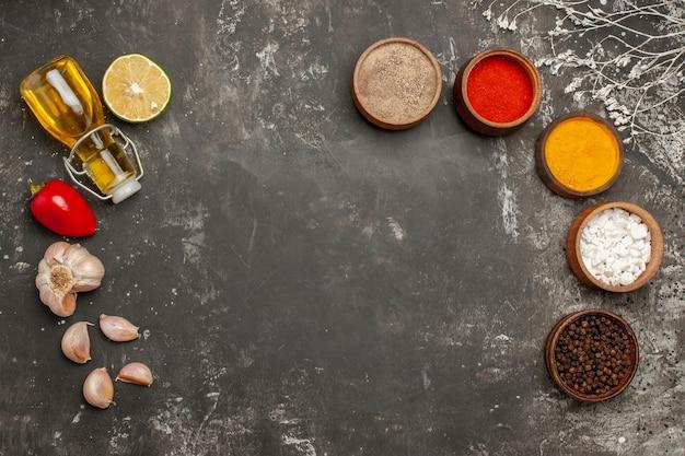 Spezie aglio peperone rosso bottiglia di olio e cinque ciotole di spezie