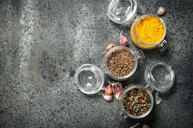 Spices in glass jars. on a rustic background.
