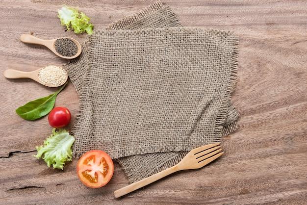 袋生地の背景にスパイス、ハーブ、野菜。上面図、フラットレイ。タイム、チリ、ペッパーコーン、レッドトマト、タマネギ、月桂樹の葉、カルダモン