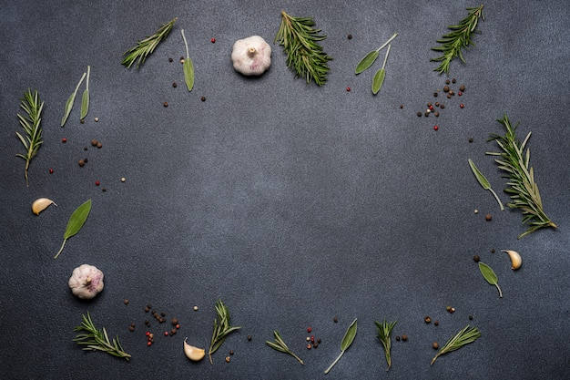 Spices and herbs on black background. rosemary, sage, pepper, garlic.
