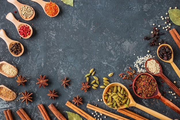Spices and herbs over black stone , flat lay..