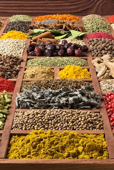 Spices and herbs collection in wooden tray.