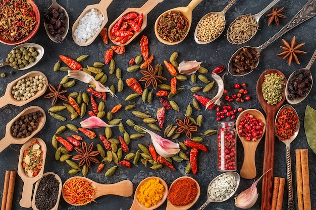 Spices and herbs for cooking in wooden spoons.