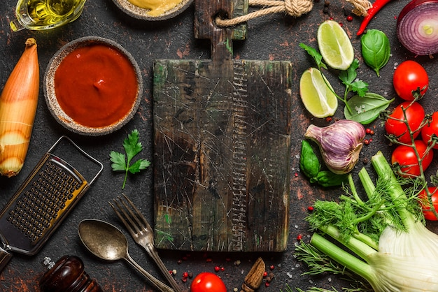 Spices, herbs and fresh vegetables with cutting board and utensils on black table