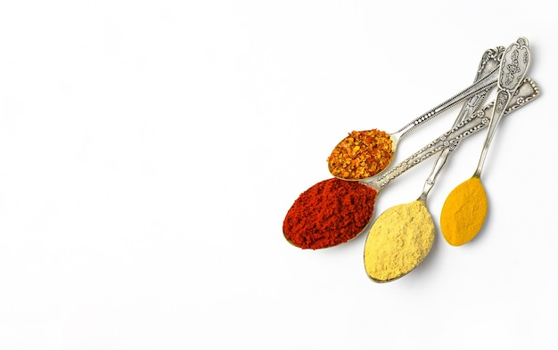 Spices and herbs in old spoons on white background