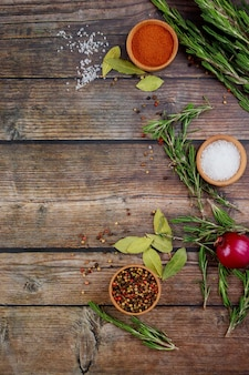 Spices and herbs on rustic wooden table. top view.