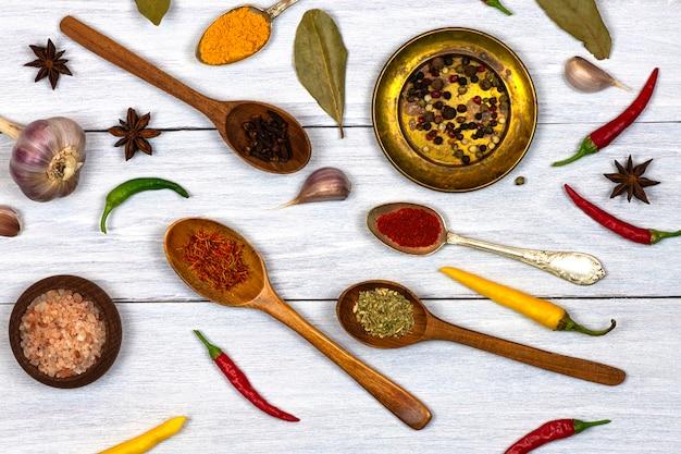 スパイス、唐辛子、スパイスのスプーン、木製の皿、白い木製の背景にブロンズプレート