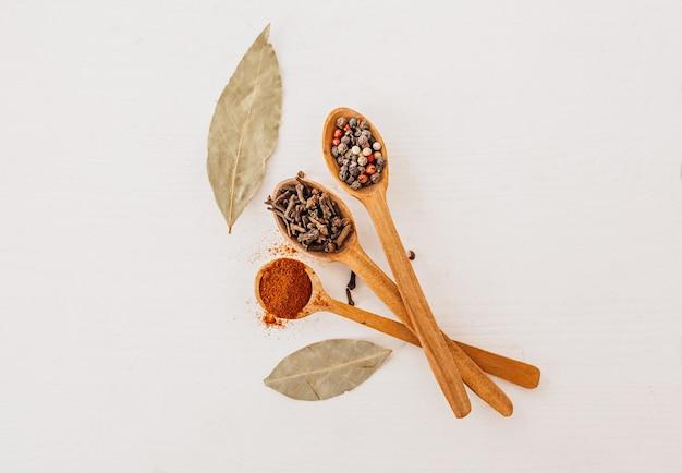 나무 숟가락에 향신료입니다. 허브, 카레, 사프란, 터메릭, 계피, 베이 리프, 흰색 배경에 요리하기 위한 고추