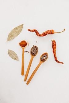 木のスプーンのスパイス。ハーブ、カレー、サフラン、ターメリック、シナモン、月桂樹の葉、白い背景で調理するためのピーマン