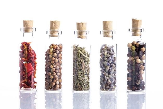 Специи в маленьких бутылочках, изолированных на белом. паприка, кориандр, розмарин, лаванда и перец горошком