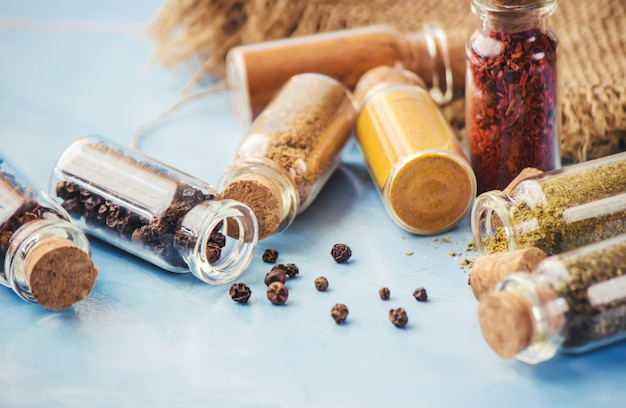 Spices in jars on wooden background. selective focus.