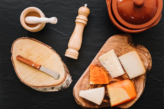 Spices and knife near cheese and pot